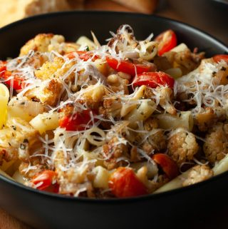 a black bowl full of roasted cauliflower, bacon, and grape tomatoes