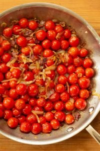 a skillet filled with bacon, onions, garlic, and grape tomatoes