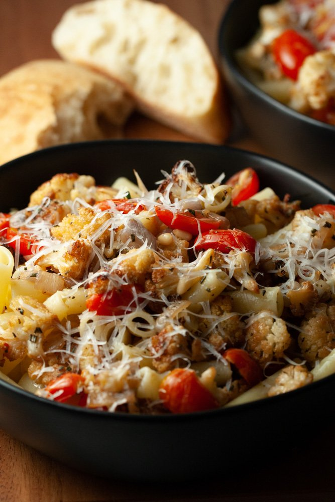 two black bowls of pasta tossed with cauliflower, bacon, and tomatoes next to chunks of warm bread.
