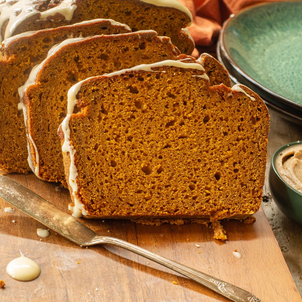 three slices of maple glazed pumpkin bread on a wooden boards with a butter knife