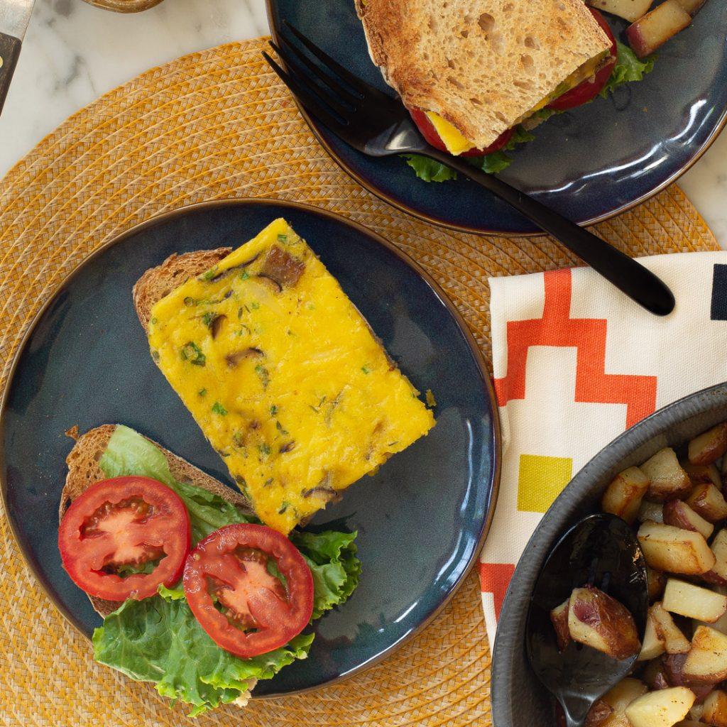 an open faced sheet pan frittata sandwich on a blue plate